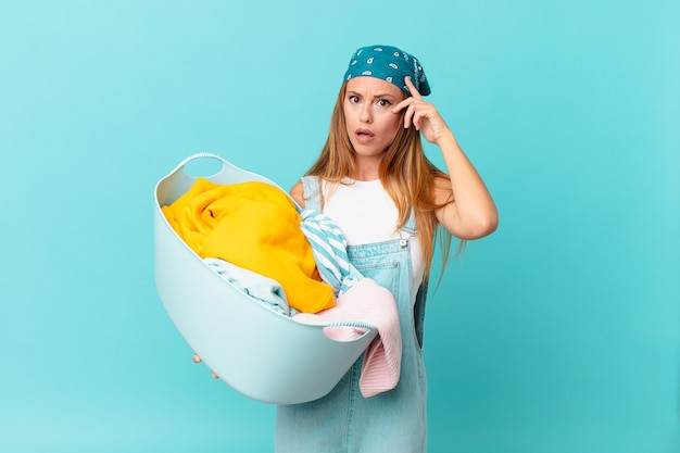 Mulher bonita parecendo surpresa, percebendo um novo pensamento, ideia ou conceito segurando uma cesta de lavagem