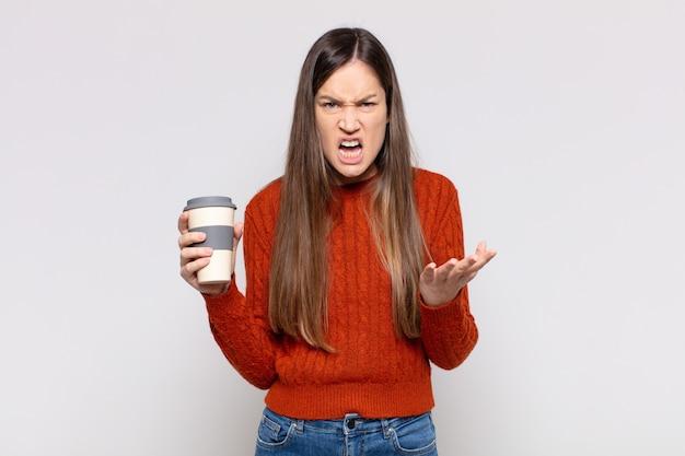 Mulher bonita parecendo zangada, irritada e frustrada gritando wtf ou o que há de errado com você Foto Premium