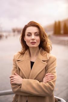 Mulher bonita parisiense com um casaco bege de outono. cabelo bonito em pé ao ar livre, posando para a câmera