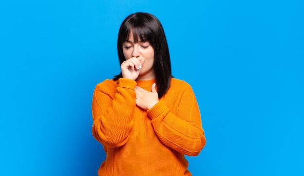 Mulher bonita passando mal com dor de garganta e sintomas de gripe, tosse com a boca coberta