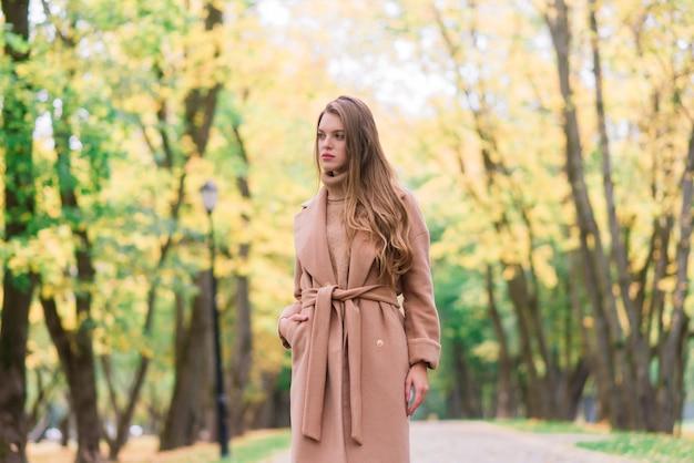 Mulher bonita passando um tempo em um parque durante a temporada de outono