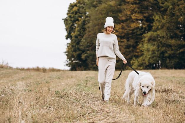 Mulher bonita, passeando com seu cachorro em um campo