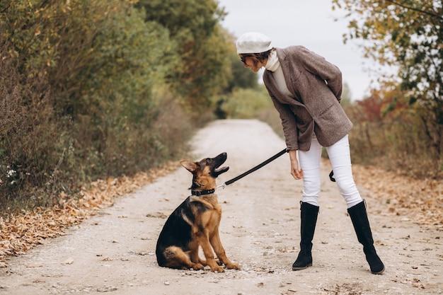 Mulher bonita, passeando com seu cachorro no parque outono