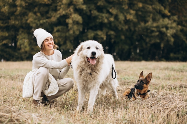 Mulher bonita, passeando com seus cães em um campo
