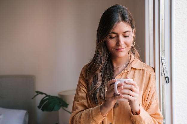 Mulher bonita pela janela em casa bebendo chá
