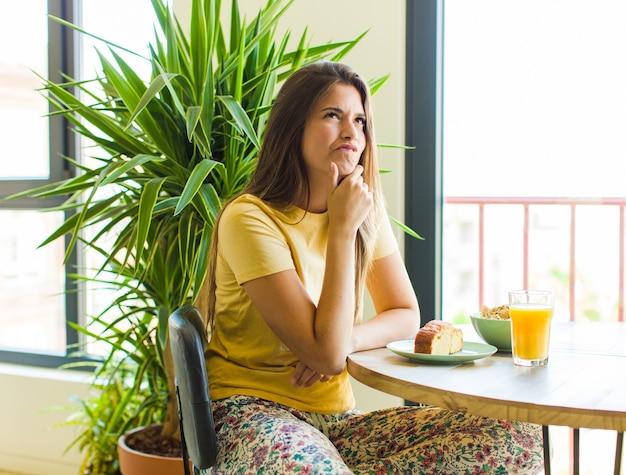 Mulher bonita pensando, sentindo-se duvidosa e confusa, com diferentes opções, imaginando qual decisão tomar