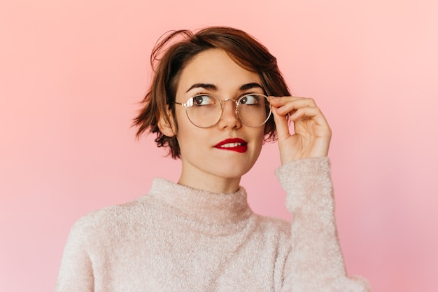 Mulher bonita pensativa a mexer nos óculos