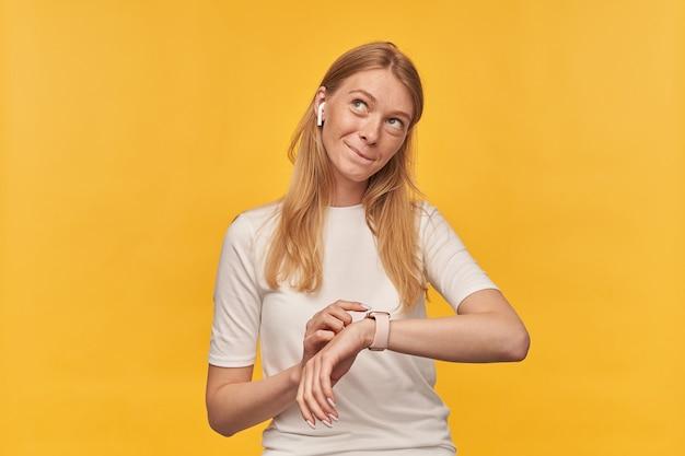 Mulher bonita pensativa com sardas em camiseta branca ouvindo música com fones de ouvido sem fio usando smart watch e pensando em amarelo