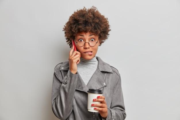 Mulher bonita perplexa morde os lábios e parece surpreendente, conversa ao telefone e bebe café para viagem, descobre notícias surpreendentes
