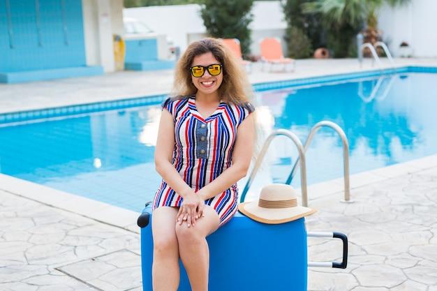 Mulher bonita perto da área da piscina com mala.