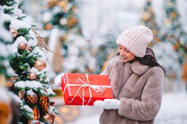 Mulher bonita perto da árvore de natal na neve ao ar livre