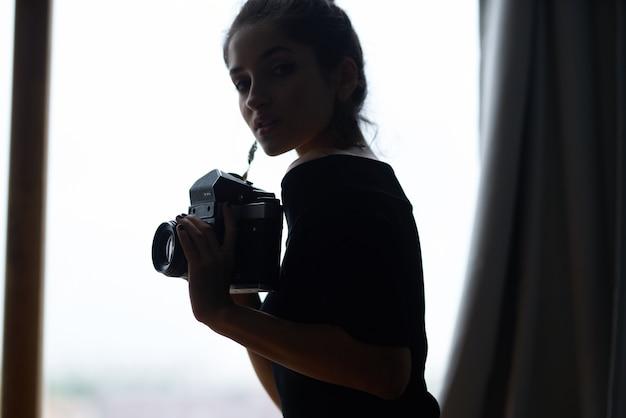 Mulher bonita perto da janela posando em estúdio de estilo de vida de brincos de aparência atraente