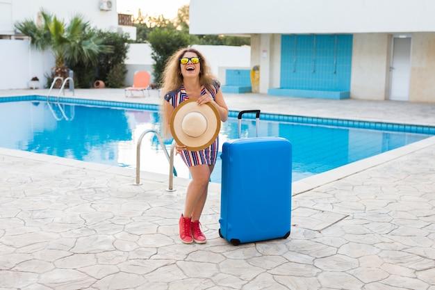 Mulher bonita perto da piscina com bagagem