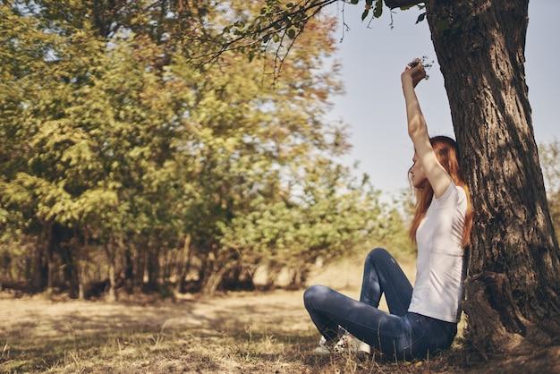 Mulher bonita perto de uma árvore ao ar livre no ar fresco da floresta e viajar