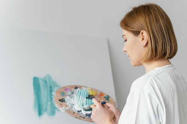 Mulher bonita pintando com acrílico sobre tela