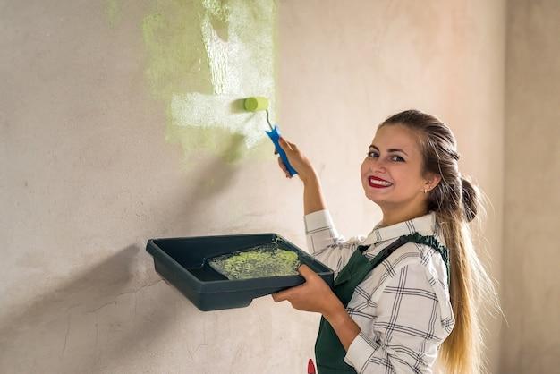 Mulher bonita pintando paredes com bandeja e rolo