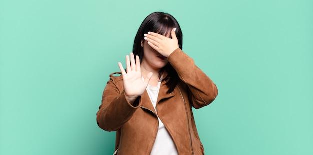 Mulher bonita plus size cobrindo o rosto com a mão e colocando a outra mão na frente para parar, recusando fotos ou imagens
