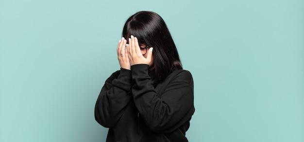 Mulher bonita plus size cobrindo os olhos com as mãos com um olhar triste e frustrado de desespero, chorando, vista lateral