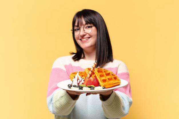 Mulher bonita plus size comendo waffles