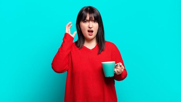 Mulher bonita plus size gritando com as mãos para o alto, sentindo-se furiosa, frustrada, estressada e chateada