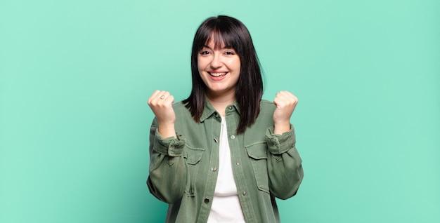 Mulher bonita plus size gritando triunfantemente, rindo e se sentindo feliz e animada enquanto celebra o sucesso