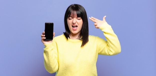 Mulher bonita plus size parecendo infeliz e estressada, gesto suicida fazendo sinal de arma com a mão, apontando para a cabeça