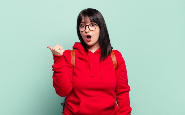 Mulher bonita plus size parecendo surpresa em descrença, apontando para o objeto ao lado e dizendo uau, inacreditável