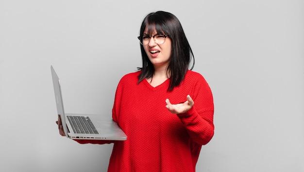 Mulher bonita plus size parecendo zangada, irritada e frustrada gritando o que há de errado com você