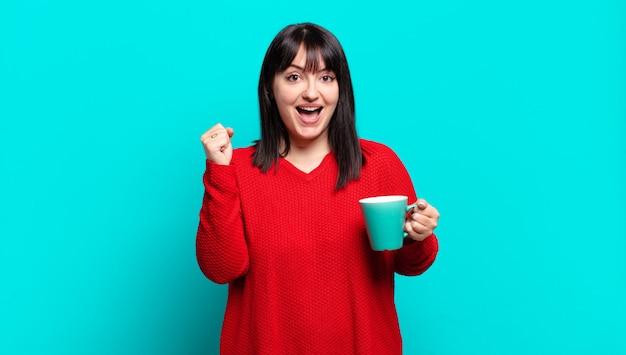 Mulher bonita plus size se sentindo chocada, animada e feliz, rindo e comemorando o sucesso, dizendo uau!