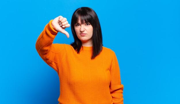 Mulher bonita plus size se sentindo zangada, irritada, irritada, decepcionada ou descontente, mostrando polegares para baixo com um olhar sério