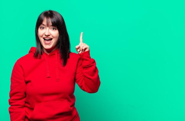 Mulher bonita plus size sentindo-se como um gênio feliz e animado depois de realizar uma ideia, levantando o dedo alegremente, eureka!
