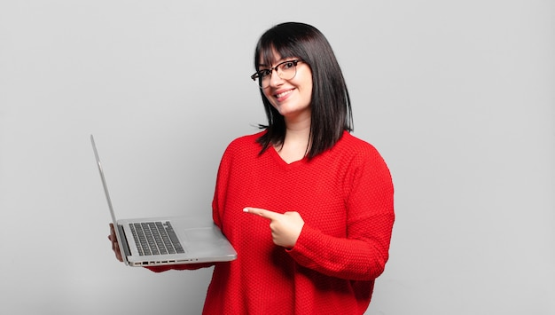 Mulher bonita plus size sorrindo alegremente, sentindo-se feliz e apontando para o lado e para cima, mostrando o objeto no espaço da cópia