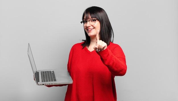 Mulher bonita plus size sorrindo com orgulho e confiança fazendo a pose número um triunfantemente, sentindo-se uma líder