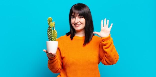 Mulher bonita plus size sorrindo e parecendo amigável, mostrando o número cinco ou quinto com a mão para a frente, em contagem regressiva