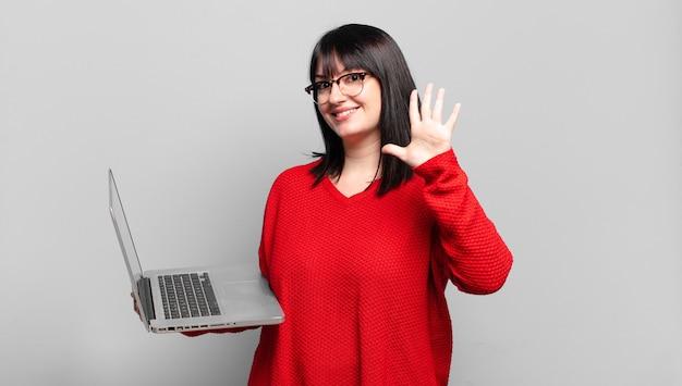 Mulher bonita plus size sorrindo e parecendo amigável, mostrando o número cinco ou quinto com a mão para frente, em contagem regressiva