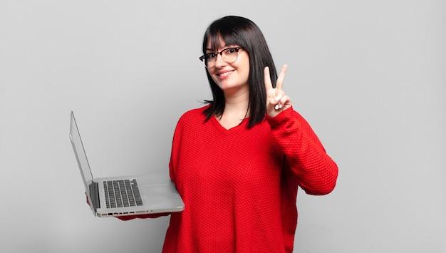 Mulher bonita plus size sorrindo e parecendo amigável, mostrando o número dois ou o segundo com a mão para a frente, em contagem regressiva