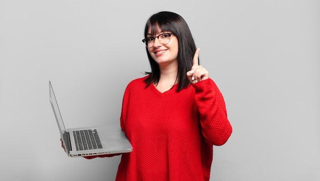 Mulher bonita plus size sorrindo e parecendo amigável, mostrando o número um ou primeiro com a mão para a frente, em contagem regressiva