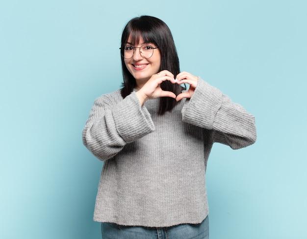 Mulher bonita plus size sorrindo e se sentindo feliz, fofa, romântica e apaixonada, fazendo formato de coração com as duas mãos