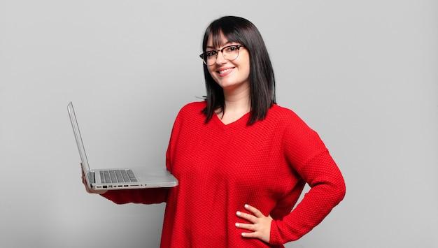 Mulher bonita plus size sorrindo feliz com a mão no quadril e atitude confiante, positiva, orgulhosa e amigável
