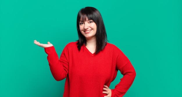 Mulher bonita plus size sorrindo, sentindo-se confiante, bem-sucedida e feliz, mostrando conceito ou ideia no espaço da cópia ao lado