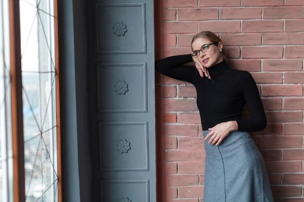 Mulher bonita posando ao lado da parede