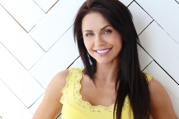 Mulher bonita posando com camiseta amarela