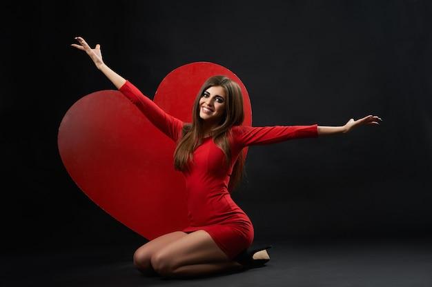 Mulher bonita posando com coração gigante
