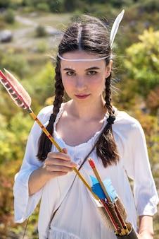 Mulher bonita posando com roupa e arma tradicionais como uma guerreira indígena ao ar livre