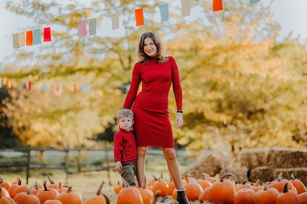 Mulher bonita posando com seu filho pequeno no campo de abóboras