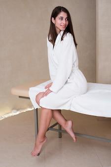 Mulher bonita posando em roupão de banho no spa