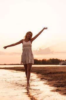 Mulher bonita posando na praia, uma jovem loira esguia em um vestido branco está girando no rio ...