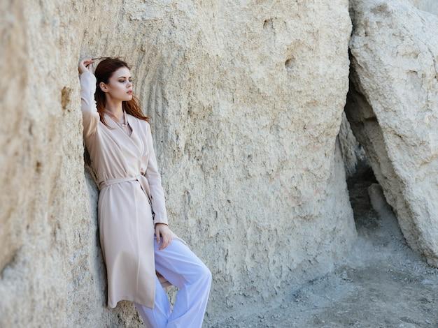 Mulher bonita posando perto de pedras na areia.