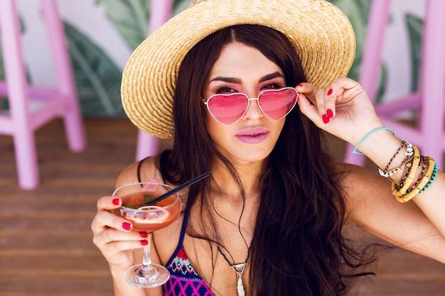 Mulher bonita praia em trajes de banho de cor brilhante, óculos de sol coração rosa e chapéu de palha, aproveitando o horário de verão