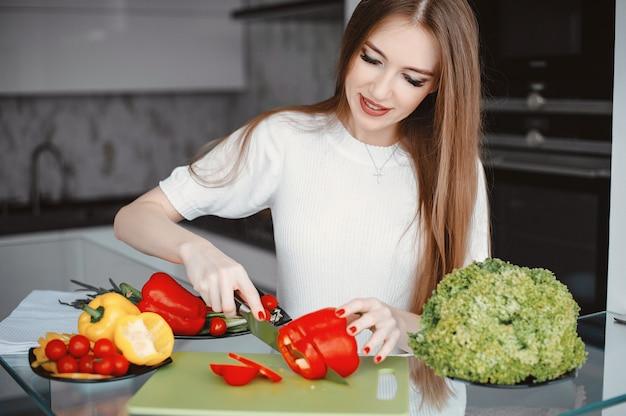 Mulher bonita preparar comida em uma cozinha